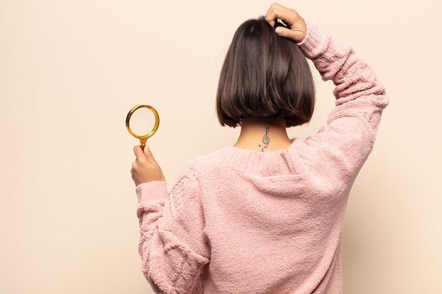 젊은 히스패닉 여자 생각 또는 의심, 머리를 긁적, 의아해하고 혼란스러운 느낌, 뒤 또는 후면보기