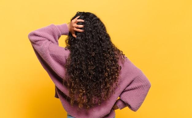 Молодая латиноамериканка думает или сомневается, почесывает голову, чувствует недоумение и замешательство, вид сзади или сзади