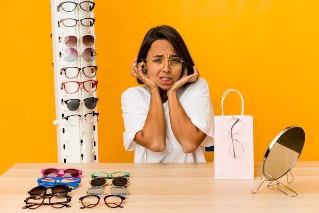 Молодая латиноамериканская женщина примеряет очки, закрывая уши руками.