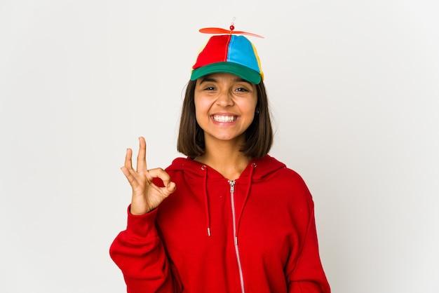 프로펠러 모자를 쓰고 젊은 히스패닉 여자는 명랑하고 자신감을 보여주는 확인 제스처를 격리합니다.