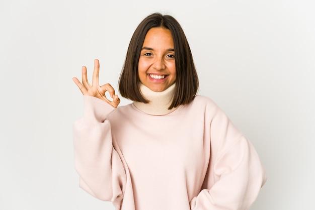 陽気で自信を持って大丈夫なジェスチャーを示す首輪を身に着けている若いヒスパニック系の女性。