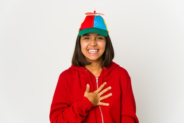 Young hispanic woman wearing a cap with propeller isolated laughs out loudly keeping hand on chest.