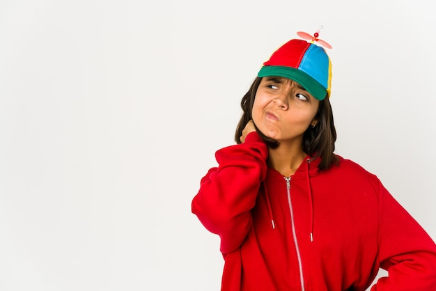 Young hispanic woman wearing a cap with propeller isolated touching back of head, thinking and making a choice.