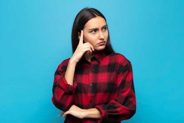 集中した表情で、疑わしい表情で不思議に思って、見上げて横を向いている若いヒスパニック系女性