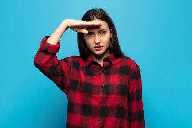 존경을 보여주는 명예와 애국심의 행동에 군사 경례를 가진 젊은 히스패닉 여성