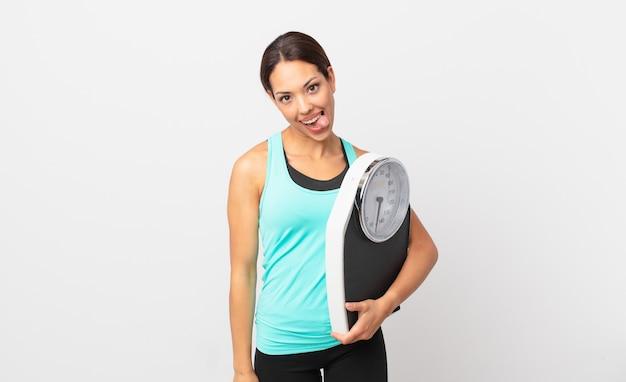 陽気で反抗的な態度、冗談を言って舌を突き出し、体重計を持っている若いヒスパニック系女性