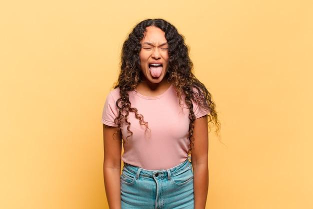 Молодая латиноамериканка с веселым, беззаботным, бунтарским настроем, шутит и высунула язык, веселится