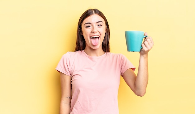 Young hispanic woman with cheerful and rebellious attitude, joking and sticking tongue out. coffee cup concept