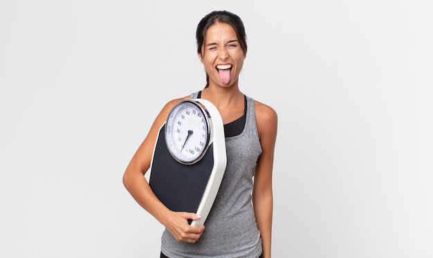 Young hispanic woman with cheerful and rebellious attitude, joking and sticking tongue out and holding a weight scale. diet concept