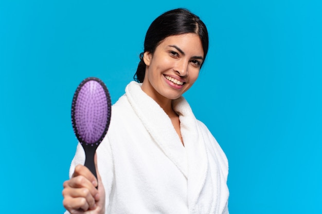 Young hispanic woman with a hair brush.