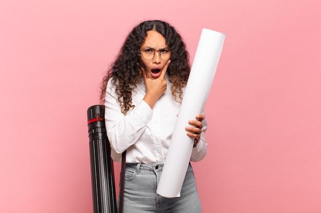 口と目を大きく開いてあごに手を当てている若いヒスパニック系の女性は、不快なショックを受けて、何を言っているのか、すごいのかと言っています。建築家の概念
