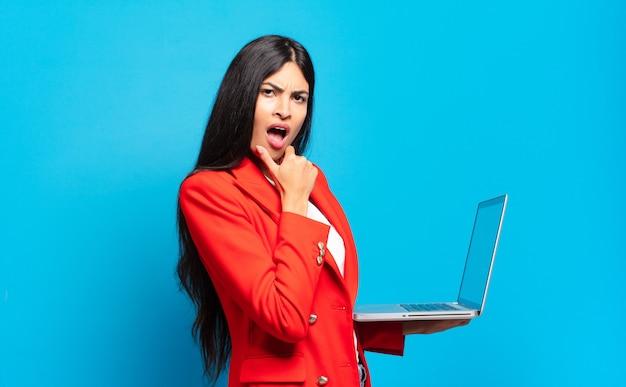 입과 눈을 크게 벌리고 턱에 손을 댄 젊은 히스패닉계 여성이 불쾌하게 충격을 받고 무엇을 말하거나 와우라고 말합니다. 노트북 개념