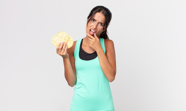 口と目を大きく開いて、あごに手を置く若いヒスパニック系女性。フィットネスダイエットのコンセプト