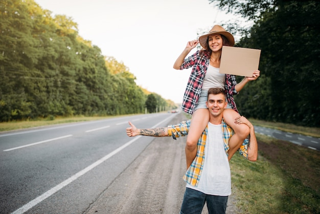 Young hitchhiking couple with empty cardboard. hitchhike adventure of man and woman. happy hitchhikers on road