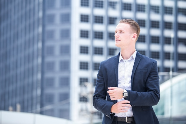 Young hnadsome businessman standing in city looking and ready for work.