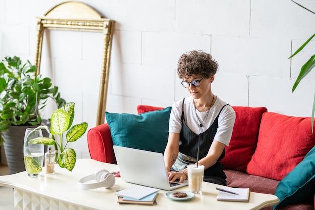 Молодой менеджер домашнего офиса в повседневной одежде сидит на диване с подушками перед ноутбуком, работая удаленно