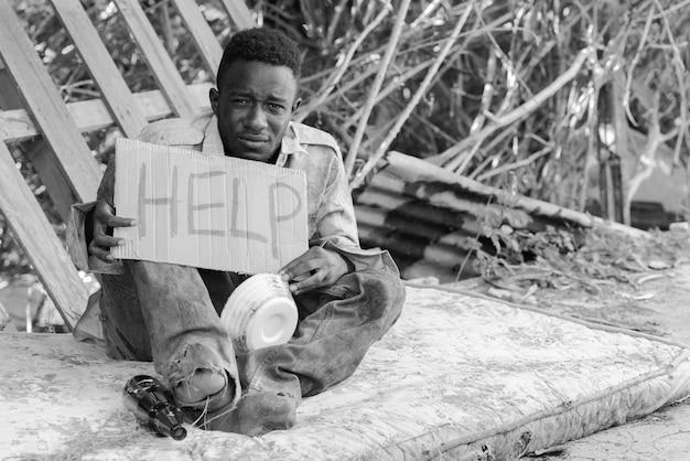 Молодой бездомный африканец с картонным знаком, просящим о помощи в черно-белом
