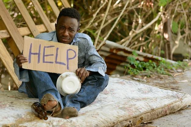 助けを求める段ボールの看板を持つ若いホームレスのアフリカ人