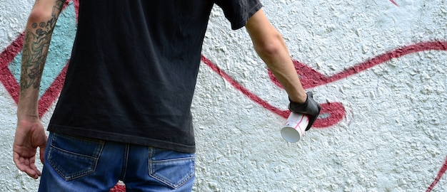A young hooligan paints graffiti on a concrete wall