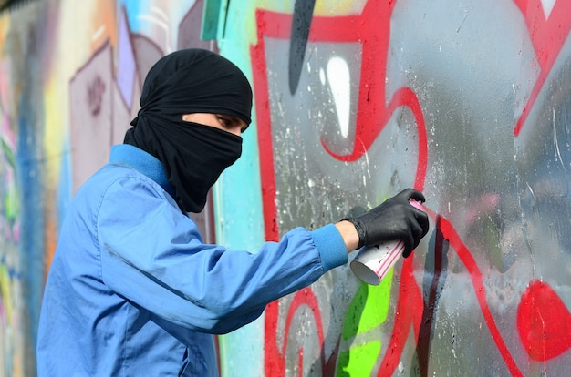 A young hooligan with a hidden face paints graffiti on a metal wall. illegal vandalism concept