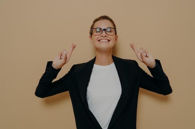 希望を持って指を交差させ、目を閉じたまま、茶色の背景の上に孤立して立っている間、願い事をしている白いtシャツの上に黒いブレザーで眼鏡をかけている若い希望に満ちた女性