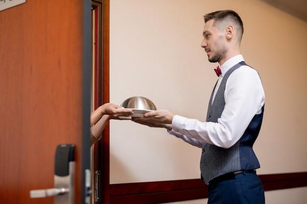 호텔 방의 문을 열고 여성 손님에게 아침이나 점심과 함께 cloche를 전달하는 제복을 입은 젊은 친절한 웨이터