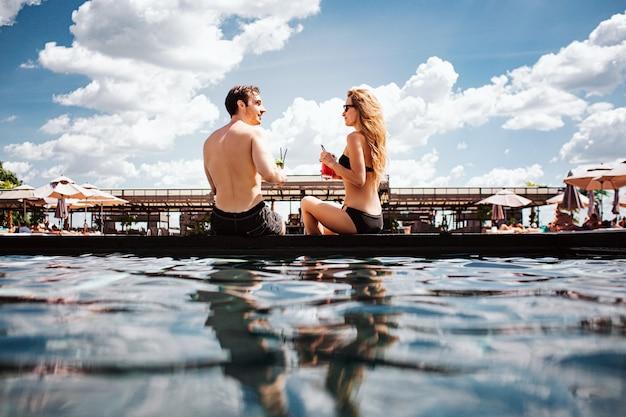 Молодая горячая пара отдыхает в бассейне