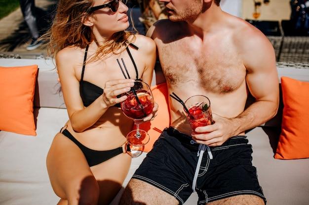 スイミングプールで休んでいる若い熱いカップル