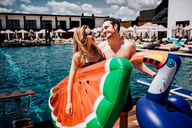 Young hot couple resting at swimpool. spend time together at water. woman and man holding two swim ring and look at each other
