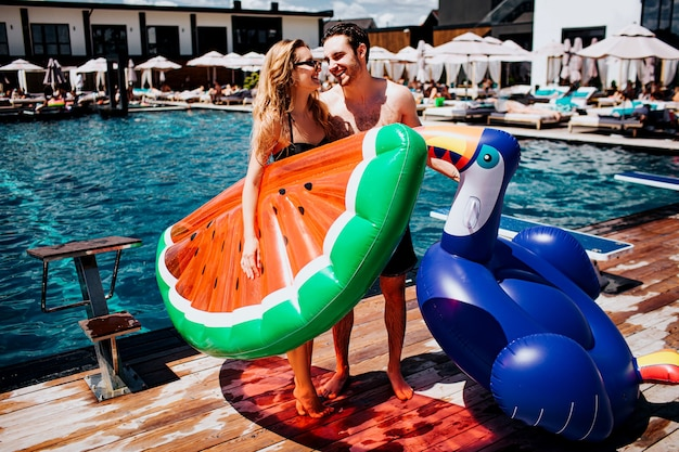 Young hot couple resting at swimpool. woman and man look at each other. holding colorful swimming rings.