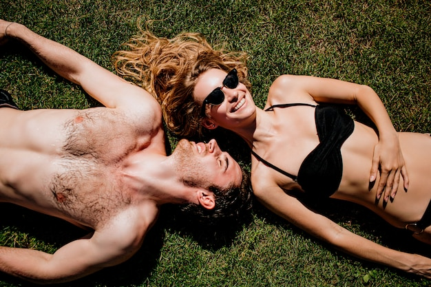 Young hot couple resting together. lying on green fresh grass and taking sunbathing