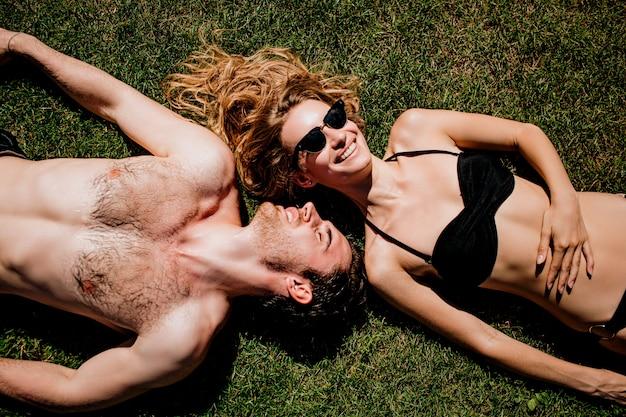 Молодая горячая пара, отдыхая вместе. лежать на зеленой свежей траве и загорать