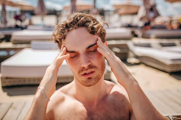 プールで頭痛を持つ若い熱い男
