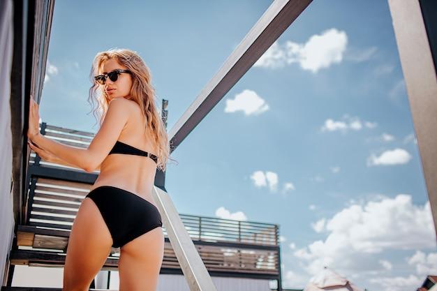 Молодая горячая женщина отдыхает в одиночестве. бакк низкий вид стройной, хорошо сложенной модели в черном купальнике, позирующей на камеру и оглядывающейся назад. стоять один снаружи и позировать.