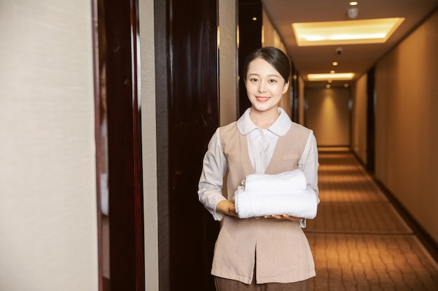 Young hotel maid cleaning hotel rooms