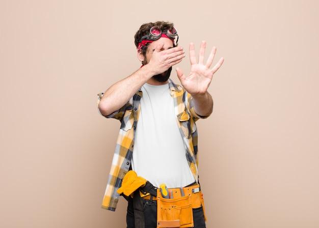若い家政婦の男の手で顔を覆い、他の手を前に置いてカメラを停止し、写真や平らな壁の写真を拒否