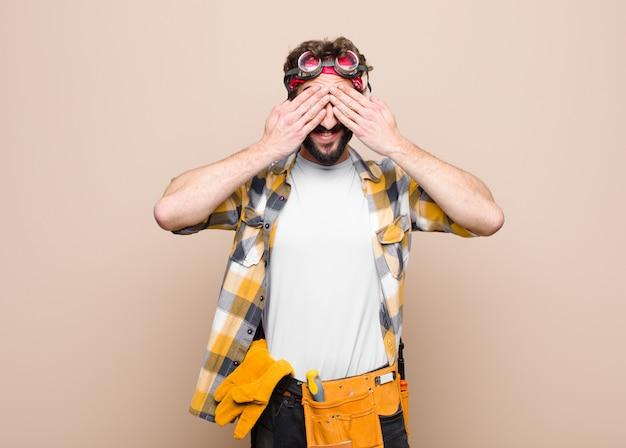 Молодой человек-домработница улыбается и чувствует себя счастливым, прикрывая глаза обеими руками и ожидая невероятного сюрприза на плоской стене