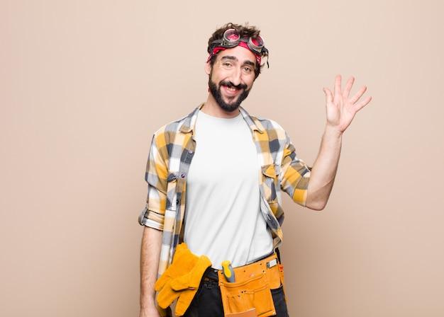 若い家政婦の男が幸せそうに笑って、手を振って、歓迎して挨拶をする、または平らな壁に別れを告げる