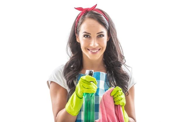 一方、クリーニングラグとカメラで洗剤を指している孤立した背景の若い家政婦。