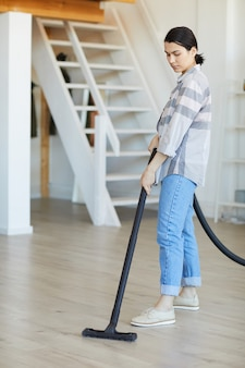 Young housekeeper vacuuming the floor at big house