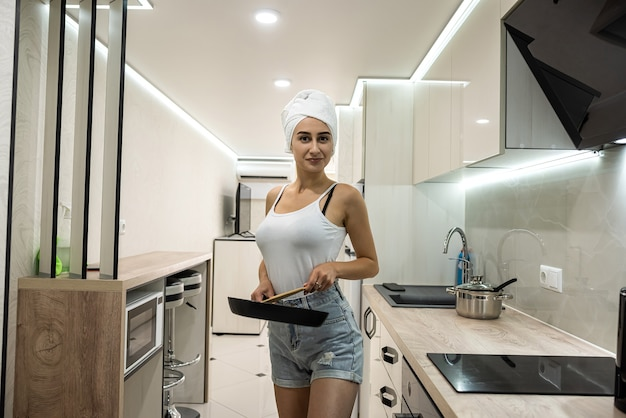 Young housewife after a shower wrapped in a white towel stands in the kitchen and prepares breakfast in a pan
