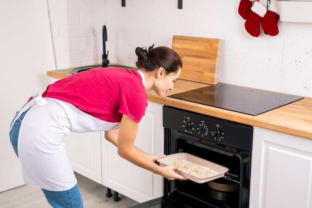 Young housewife in apron putting tray with raw cookies into open oven while bending over stove in the kitchen