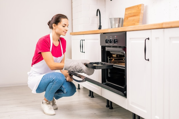 Young housewife in apron squatting while putting tray with raw cookies into electric oven while in the kitchen
