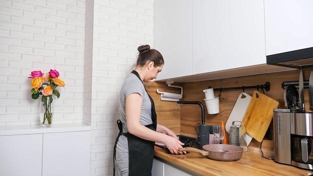젊은 주부는 싱크대에서 씻을 더러운 접시 더미를 운반하고 세련된 가구가 있는 현대적인 주방에서 검은 앞치마에 손을 닦습니다