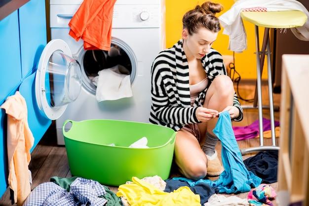 Молодая домохозяйка проверяет одежду, сидя на полу возле стиральной машины дома
