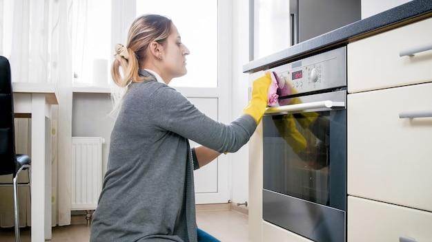 調理後のキッチンのオーブンの掃除と磨きをする若い主婦。