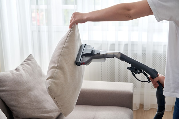 Young housewife cleaning sofa with vacuum cleaner in living room