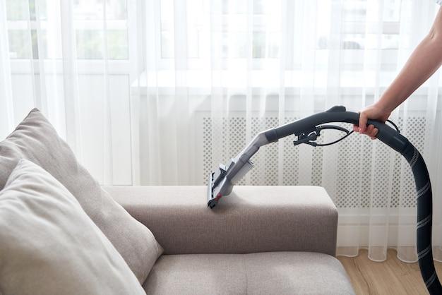 Молодая домохозяйка чистит диван пылесосом в гостиной