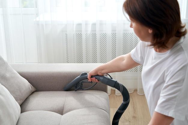 Молодая домохозяйка убирает диван пылесосом в гостиной