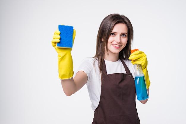 Молодая домохозяйка убирает коврик и моющее средство изолированы